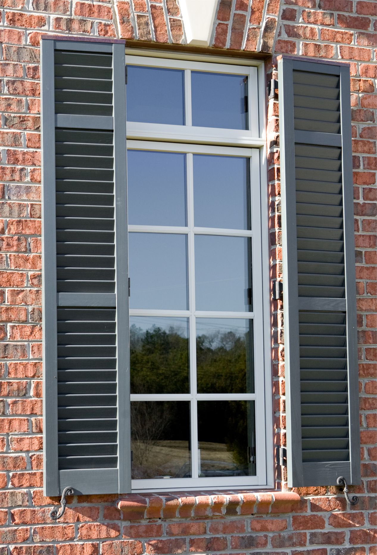 Exterior window shutters on brick home.