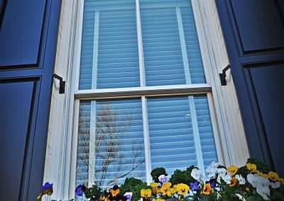 Outdoor shutters of Harmony Raised Panel Shutters with quarter top configuration.