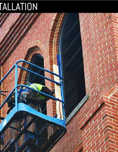 Worker installing new, custom louvered shutters at church bell tower.