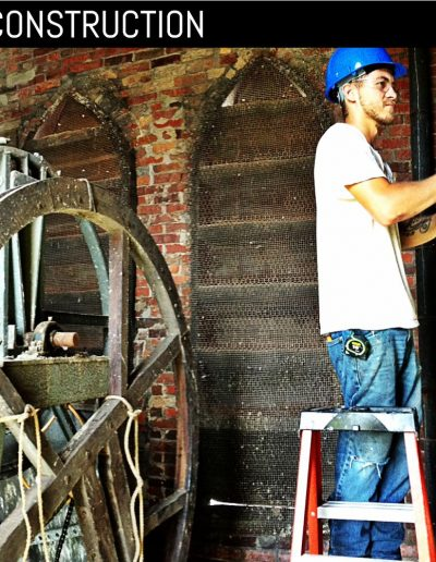 Worker removing antique louvered shutters from inside of bell tower.