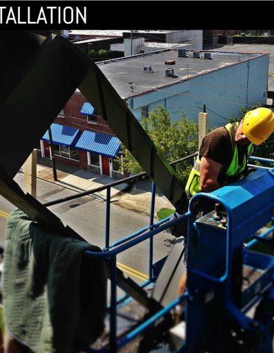 Worker moving custom, louvered shutter frame through open bell tower window.